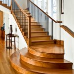 Photo of straight stair with wrought iron balusters and dramatic round starting steps.