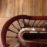 Photo taken from above of a multilevel curved staircase with wrought iron balusters.