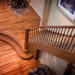 Photo taken from above of a curved stair with wrought iron balusters.