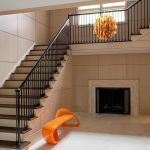 Photo of a modern styled straight stair with wrought iron balusters.