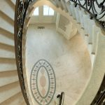 Photo taken from above of a dramatic curved stair with custom wrought iron balusters and stone treads and risers.