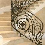 Photo of a dramatic curved stair with custom wrought iron balusters and stone treads and risers.
