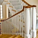 Straight staircase with white balusters and custom turned newel posts.