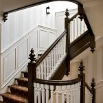 Photo of a straight stair with wood balusters and custom newels in a historic home.