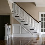 Straight stair with box newels and wood balusters. Stair features paneled wainscoting.