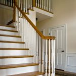 Photo of an over-the-post L-shaped stair with wood balusters.