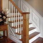 Photo of a straight stair with box newels and wood balusters. Stair features wood paneling wainscoting.