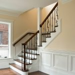 Photo of a L-shaped stair with wrought iron balusters.