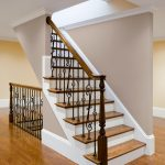 Photo of a stair with wrought iron balusters and turned wood newels post.