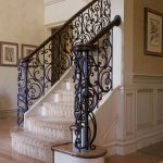 Photo of a stair with custom wrought iron balustrade and custom curved handrail. Stair flairs at bottom.