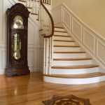 Photo of a flared stair with wood balusters and a curved handrail. Stair features paneled wainscoting.