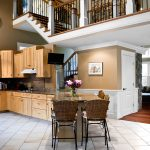 Photo of a kitchen with a stair and balcony above. Balcony features wrought iron balusters and box newels.