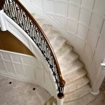 Photo taken from above of curved stair with custom wrought iron balusters.