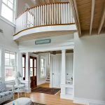 Photo of a grand foyer in a coastal home. A curved balcony features wood balusters and a curved railing.
