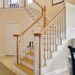 Photo of a L-shaped over-the-post stair with wood balusters.
