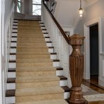 Photo of a stair with a grand custom carved newel post and wood balusters.
