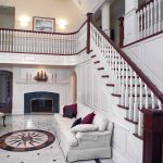 Photo of a grand foyer with a large straight stair with wood balusters, box newels, and a large balcony.