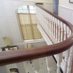 Large curved balcony with wood balusters.