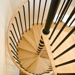 Spiral staircase with black balusters.