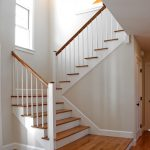 Photo of a scissor stair with wood balusters and square newel posts. The newel posts feature a round custom cap.