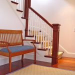 Photo of a L-shaped straight stair with box newels and custom wood balusters.