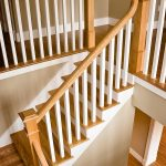 Photo taken from above of a L-shaped straight stair with box newels and wood balusters.