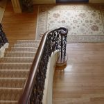 Photo taken from above of a flared stair with custom wrought iron balusters.