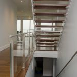 Modern stair with glass railing and open risers.