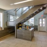 Commercial staircase with glass railing and open risers. ADA compliant handrail.