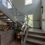 Photo of a commercial staircase with glass railing and open risers. ADA compliant handrail.