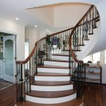 Unsupported curved stair with wrought iron balusters.