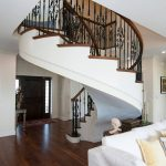 Photo of an unsupported curved stair with wrought iron balusters.