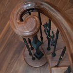Photo taken from above of a stair with a wood volute.