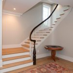 Photo of a curved winding staircase with wood balusters and a curved handrail.