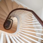Photo of a multi-level curved stair from top floor. Stair features wood balusters and a curved handrail.