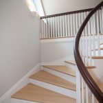 Curved winding staircase with wood balusters and a curved handrail.