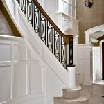 Photo of curved stair with custom wrought iron balusters. Stair features panel detailing and stone treads and risers.