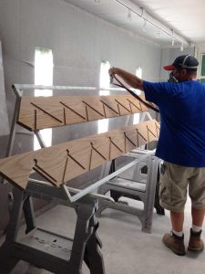 photo of tech spraying stair skirt with clear coat