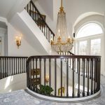 Custom curved preassembled staircase with white oak treads and scotia, primed butress style stringer, primed risers, custom bronze balusters, and 6014 sapele mahogany rail.